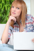 Red-haired girl sitting on sofa with laptop — Stock Photo
