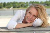 Relaxed happy woman sitting on the waterfront — Stock Photo