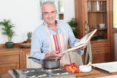 Man preparing a meal with the help of a cookbook — Stock Photo