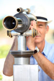Middle-aged man looking through telescope — Stock Photo