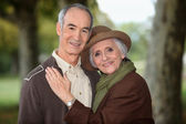 Older couple enjoying an autumnal stroll — Stock Photo