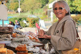 A senior woman in an open-air market — Stock Photo