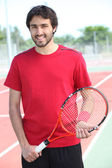Casual tennis player standing on a hard court — Stock Photo