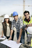 A team of tradespeople discussing a blueprint — Stock Photo