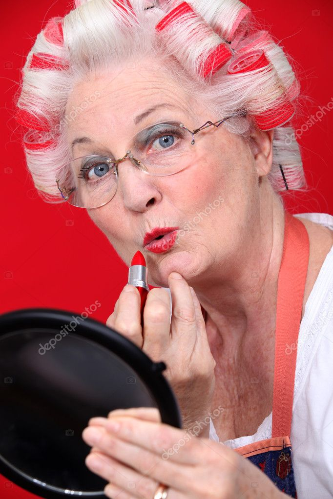 Grandmother with her hair in rollers applying lipstick — Stock Photo #7661703