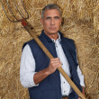 Farmer holding a pitchfork - Stock Photo