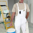 Painter carrying large pot of paint - Stock Photo