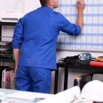 Young technician writing on a calendar — Stock Photo