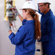Stock Photo: Young female electriciusing ammeter for checking electricity met