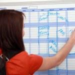 Girl writing on calendar — Stock Photo