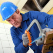 Plumber sawing a pipe — Stock Photo
