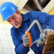 Stock Photo: Plumber sawing pipe