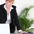 Stock Photo: Businesswoman standing at her desk