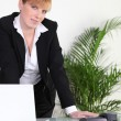 Businesswomstanding at her desk — Stock Photo #7673802