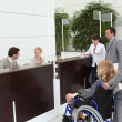 Businesswoman in a wheelchair with her colleagues at reception — Stock Photo #7674379