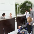 Businesswoman in a wheelchair with her colleagues at reception — Stock Photo