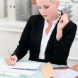 Stock Photo: Young businesswoman writing notes at her desk