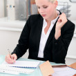 Foto Stock: Young businesswoman writing notes at her desk