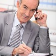 Older businessmusing cellphone — Stock Photo #7674591