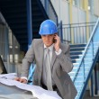 Architect on site with plans and cellphone — Stock Photo