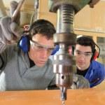 Blue collars using drillhead in workshop — Stock Photo