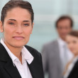 Portrait of a businesswoman with colleagues out of focus in the background — Stock Photo