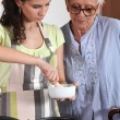 Woman using a pestle and mortar in the kitchen — Stock Photo