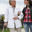Young woman helping elderly person to walk with a crutch - Stockfoto