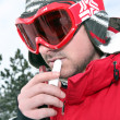 Skier applying lip balm — Foto de stock #7675821