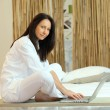 Brunette working on laptop in Zen atmosphere — Stock Photo #7676473