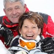 Senior couple having fun under snow — Stock Photo