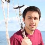 junger Mann auf Segelboot vor der Küste — Stockfoto