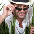 Man on holiday wearing sunglasses - Stock Photo