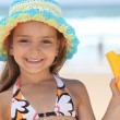 Little girl on beach with sun cream — Stock Photo #7677080
