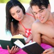 Couple reading on the beach — Stock Photo