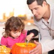 Stock Photo: Father and daughter carving pumpkins