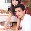 Young couple doing paperwork at the kitchen table — Stok fotoğraf