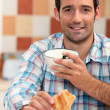 Man reading a newspaper at breakfast — Stock Photo