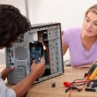 Stock Photo: Mrepairing computer under his wife's