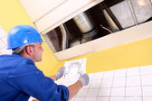 Craftsman dressed in blue jumpsuite is reading a draw and watching air cond — Stock Photo
