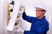 Electrician with a fusebox — Stock Photo