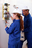 A young female electrician using an ammeter for checking an electricity met — Stock Photo