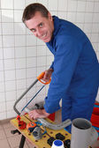 Smiling plumber sawing plastic pipe — Stock Photo