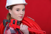 Craftswoman holding a pipe hose and a spanner — Stock Photo