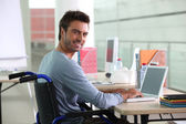 Man sitting at desk in wheelchair — Stock Photo