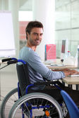 Man in wheelchair working at computer — Stock Photo
