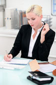 Young businesswoman writing notes at her desk — Foto de Stock