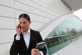 Businesswoman on a cellphone outside an office building — Stock Photo