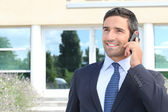 Smiling man in suit talking on cellphone — Stock Photo