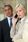 Blond woman on phone next to director — Stock Photo